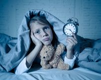 Little Girl in bed awake at night yawning and feeling restless showing clock she can not sleep. Cute sleepless little girl lying in bed showing alarm clock royalty free stock images