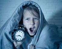 Little Girl in bed awake at night yawning and feeling restless showing clock she can not sleep. Cute sleepless little girl lying in bed showing alarm clock stock photography