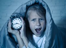 Little Girl in bed awake at night yawning and feeling restless showing clock she can not sleep. Cute sleepless little girl lying in bed showing alarm clock stock photos