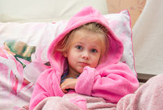 Little girl in bed bewildered looks into the camera. Little girl in bed in a warm bathrobe bewildered looks into the camera Stock Photos