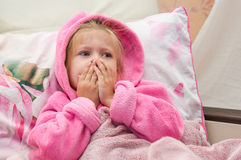 Little girl in bed  bewildered looks into the camera. Little girl in bed in a warm bathrobe bewildered looks into the camera Royalty Free Stock Image