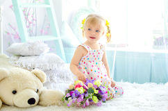 Little girl on bed with flowers and big teddy bear. Little cute girl sitting on bed in light bedroom with bouquet of flowers and big white teddy bear stock photos