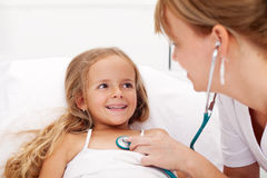 Little girl in bed having a health check Stock Image