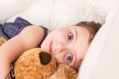 Little girl in bed hugging teddy bear. Royalty Free Stock Photography