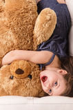 Little girl in bed hugging teddy bear. Royalty Free Stock Photo