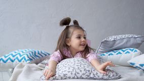 Little girl in bed lying on pillows. Happy childhood. stock footage