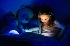 Little girl in bed with night lamp Royalty Free Stock Photography