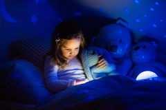 Little girl in bed with night lamp Royalty Free Stock Photos