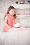 Little girl on a bed with pink box Stock Images