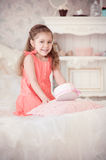 Little girl on a bed with pink box Stock Photos