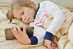 Little girl  in bed with smartphone Stock Images