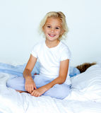 Little girl in bed smiling at the camera Stock Images