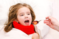 Little girl in bed taking medicine with spoon Stock Photography
