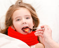 Little girl in bed taking medicine with spoon Stock Photo