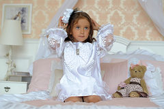 Little girl  on a bed with teddy bear Royalty Free Stock Photos