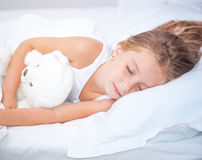 Little girl in the bed with teddy bear royalty free stock photography
