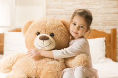 Little girl in bed with teddy bear Stock Photo