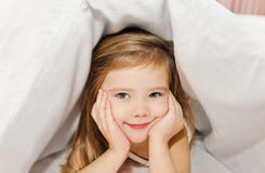 Little girl in the bed under cover Royalty Free Stock Images