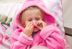 Little girl in bed  vysmarkivaet nose into a napkin Stock Photo