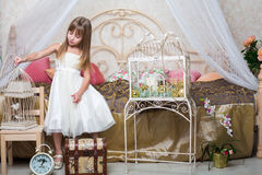 Little girl in the bedroom holding a cage Stock Image