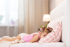 Little girl in the bedroom is lying on the bed on the pillow and Stock Photo