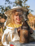 Little girl beekeeper blows smoker for bees Stock Photography