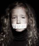 Little girl begging for help. Little child with taped mouth, begging for help. Sad, abuse girl. Violence, despair Stock Photo