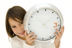 Little girl behind a clock Stock Photography
