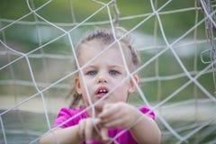 Little girl behind football net. Little girl staying behind football net and playing with it Stock Images