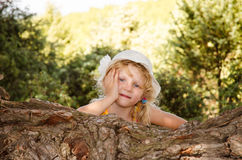 Little girl behind tree trunk portrait Stock Photo