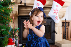 Little girl being happy about christmas tree and lights Stock Photo