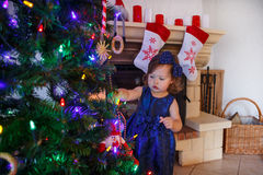 Little girl being happy about christmas tree and lights Stock Images