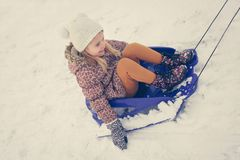 Little girl being pulled on a sled. stock photography