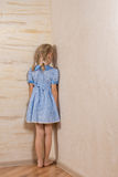 Little girl being punished standing in the corner. Facing into the wall in her pretty blue dress and bare feet stock image