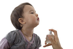 Little girl being scented by her mother Stock Images