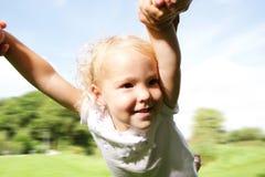 Little girl being spun in circles Stock Photos