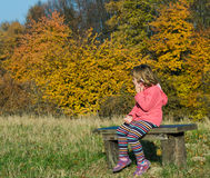 Little girl on the bench. Little girl sitting on the bench in the woods,speaks by phone Royalty Free Stock Photography