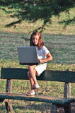 Little girl on a bench with computer Royalty Free Stock Image