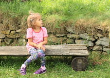 Little girl on bench Stock Images