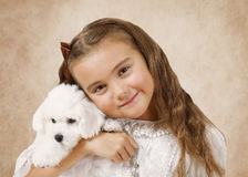 Little girl with Bichon Frise puppy. Portrait of a little girl with Bichon Frise puppy on a beige background Royalty Free Stock Photos