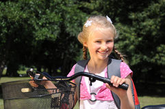 Little girl on a bicycle. Portrait of a little girl on a bicycle in summer park outdoors Royalty Free Stock Photo