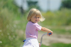 The little girl on a bicycle. Looks back Stock Images
