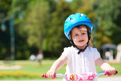 Little girl with bicycle Stock Images