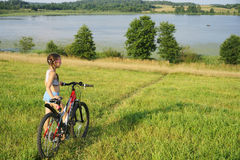 Little girl with bicycle in field Royalty Free Stock Images