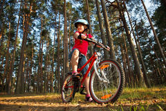 Little girl with bicycle in the forest Stock Image