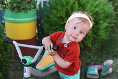 Little girl on bicycle. Kid biking outdoors in village. Stock Image