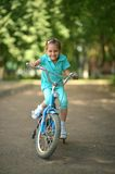 Little girl with bicycle. Outdoors in summer Stock Photos