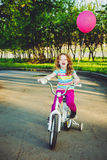 Little girl on bicycle in the park. Background toning for instagram filter Royalty Free Stock Photography