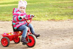 Little girl on a bicycle. Portrait of a little girl on a bicycle in autumn  park outdoors Royalty Free Stock Photography