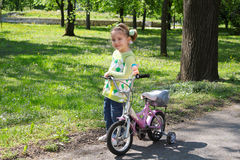 Little girl with bicycle posing Stock Photography